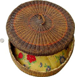 A small domestic basket holding a yellow cushion